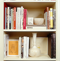 Close up of books, drawings and ceramics arranged on a custom made bookcase
