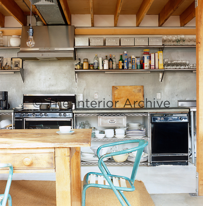 Organised along a single wall, free-standing stainless steel fittings, a blue-stone worktop and a professional cooker are compatible with the raw industrial structure of this kitchen