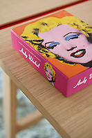 A box of Andy Warhol postcards on a desktop in the bedroom