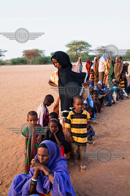 Somali women and their children wait in a queue outside a registration point at the IFO camp part of the Dadaab refugee camp in Kenya. The drought is the worst in East Africa for 60 years. The UN described it as a humanitarian emergency. The already overcrowded complex received 1,000 new refugees a day in June, five times more than a year ago. About 30,000 people arrived at the Dadaab refugee camp in June, according to UNHCR compared to 6,000 in June 2010.