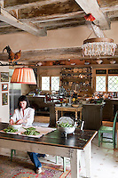 Portrait of chef Maddalena Caruso in her large country kitchen shelling freshly picked peas from her vegetable garden