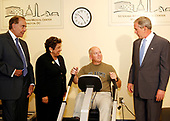 Washington, D.C. - August 14, 2007 -- Sergeant Major Mike Welsh (retired), right center, demonstrates how to use the Nu Step Machine as United States President George W. Bush, right, visits the DC Veterans Affairs Medical Center accompanied by Secretary of Veterans Affairs James Nicholson, not pictured, Deputy Secretary of Defense Gordon England, not pictured, and the two Co-chairs of the Presidential Commission to study the quality of Veterans Healthcare Donna Shalala, center left, and former US Senator Bob Dole (Republican of Kansas), left, look on on Monday, August 14, 2007. The tour was lead by the Director of the DC Veterans Affairs Medical Center  Fernando Rivera, not pictured. The President visited the Rehabilitation Room, in which patients receive intensive rehabilitation, including physical therapy, accupational therapy, cognitive and speech therapy. The President also visited the indoor pool in which patients receive physical, cardiac and recreation rehabilitation through aquatic therapy.<br /> Joe Mornini, Founder of Team River Runner, offered a demonstration showcasing severaly wounded patients and their newly learned mobile skills. Team River Runner is an all-volunteer organization established  in August 2004 by kayakers. <br /> Credit: Aude Guerrucci - Pool via CNP