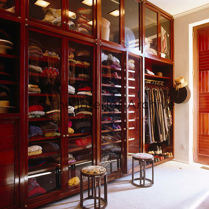 Glass-fronted drawers in this bespoke wardrobe are filled with neat piles of folded sweaters, next to tidily arranged pairs of shoes and serried ranks of coats on hangers.