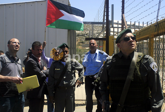 A Palestinian holds up a flag during a protest outside Ofer prison near the West Bank city of Ramallah May 13, 2010, against the deportation by Israel of Palestinian prisoners to the Gaza Strip. photo by Issam Rimawi