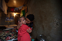 Tlbech, 27 years old, and her son Zarhiun, 4, both HIV positive hug after Zarihun expressed his sadness for the possibility of losing his mom, in their small house in one of the poorest neighborhoods in Addis Ababa, ethiopia on thursday July 27 2006..Talbech and Zarihun live on a 180 birr ( 20 USD ) per month sponsorship from the HfC NGO. they spend 100 Birr for rent leaving less than 10 USD for food and other necessities. Nevertheless they are a privileged family in the country..Tlbech besides fighting againt the virus and taking care of her child provides home base care assistance in Addis to other HIV patients in need..Ethiopia is one of the countries most affected by HIV/AIDS. Of its population of 77 million, three million are HIV-positive, according to government statistics. Every day sees 1,000 new infections. A million children under 14 have lost one or both parents to AIDS, and 200,000 children are living with AIDS. That makes Ethiopia the country with the most HIV-positive children.