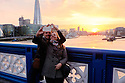 London, UK. 07.04.2015. Young couple taking a selfie on Tower Bridge, London, UK.  Photograph © Jane Hobson.