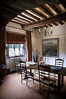 The traditional dining room is graced with a pair of contemporary paintings
