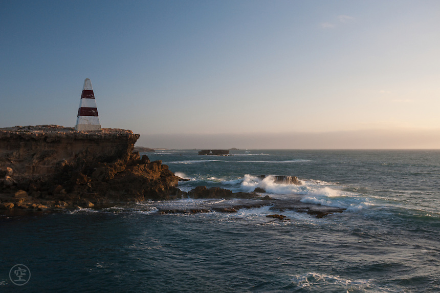 A windy evening and breakers crash against the crumbling limestone islands and the peninsula where Robe's famous landmark, the Obelisk, precariously stands.
