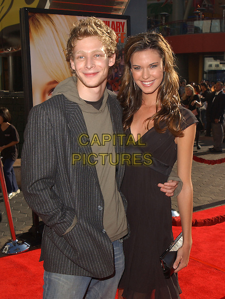 JOHNNY K. LEWIS & GIRLFRIEND.The New Line Cinema's World Premiere of Raise Your Voice held at The Loews Universal City 18 Theatres in Universal City, California .October 3, 2004.half length, arm around waist, hand in pocket, pimstrip jacket.www.capitalpictures.com.sales@captialpictures.com.Copyright 2004 by Debbie VanStory