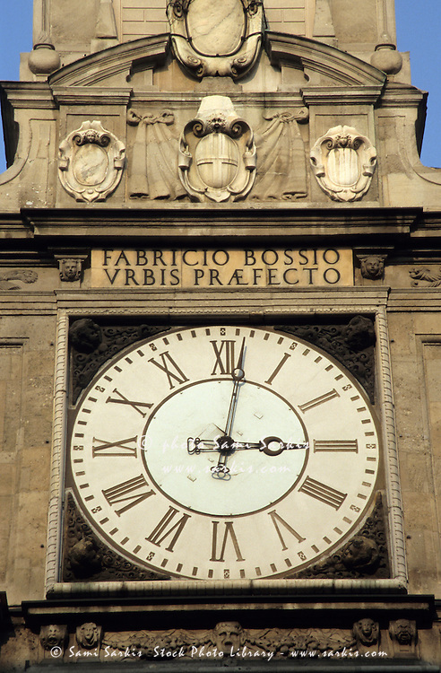 Clock and inscription on a tower, Milan, Italy.