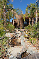 Lush landscaping leads to pool area with water features