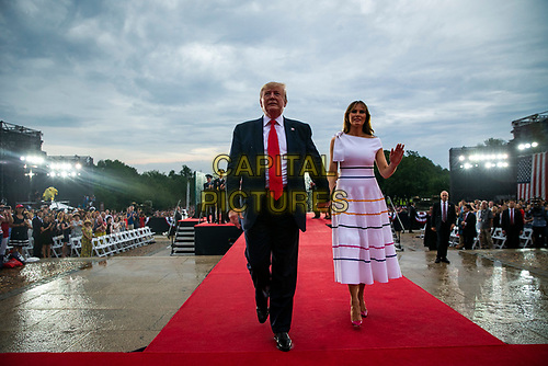"U.S. President Donald Trump waves with first lady Melania Trump during the Fourth of July Celebration 'Salute to America' event in Washington, D.C., U.S., on Thursday, July 4, 2019. The White House said Trump's message won't be political -- Trump is calling the speech a ""Salute to America"" -- but it comes as the 2020 campaign is heating up. <br /> h<br /> CAP/MPI/CNP<br /> ©CNP/MPI/Capital Pictures"