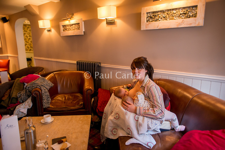 A woman breastfeeding her 5 month old  twins in tandem in the lounge bar of a pub.<br /> <br /> Image from the &quot;We Do It In Public&quot; documentary photography project collection: <br />  www.breastfeedinginpublic.co.uk<br /> <br /> Hampshire, England, UK<br /> 11/02/2013