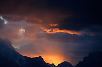 Sunset illuminates dark clouds over the mountains of Grand Teton National Park, Wyoming.