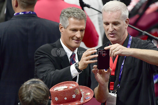 Former United States Senator Scott Brown (Republican of Massachusetts), left, poses for a photo with an unidentified man at the 2016 Republican National Convention held at the Quicken Loans Arena in Cleveland, Ohio on Wednesday, July 20, 2016.<br /> Credit: Ron Sachs / CNP/MediaPunch<br /> (RESTRICTION: NO New York or New Jersey Newspapers or newspapers within a 75 mile radius of New York City)