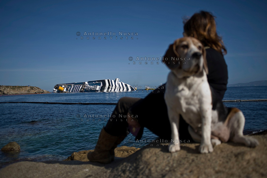 Island of Giglio, Italy, January 21, 2012.  A woman looks at the stricken cruise liner Costa Concordia off the Tuscan island of Giglio..