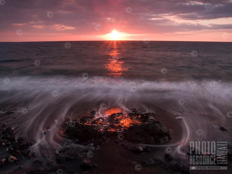 Water caresses lava rock as it flows back toward the sunset, North Kohala, Big Island.