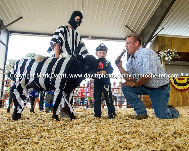 Jackson Arenson dress as a policeman and calf as a prisoner gets interviewed before his run in the Bucket Calf event during the Warren County Fair.