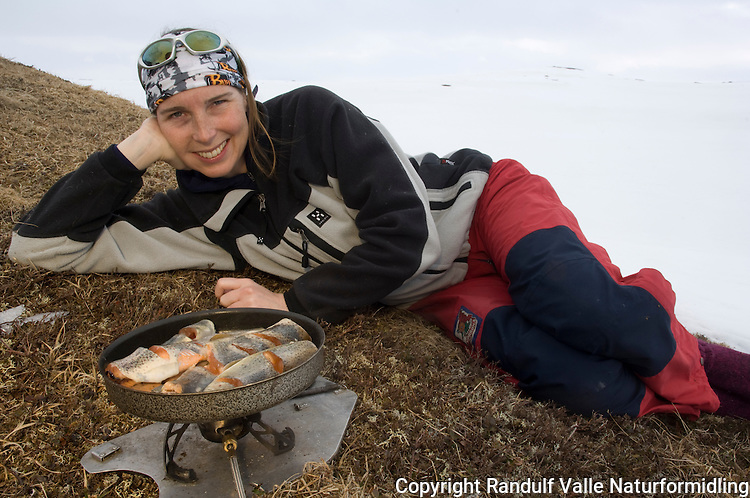 Jente på barflekk i fjellet venter på at fisk skal stekes ---- Girl waiting for trout to cook