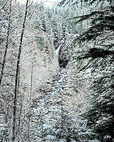 Lower Twin Falls and South Fork Snoqualmie River flow through a frosted winter forest. Olallie State Park, North Bend, Washington State