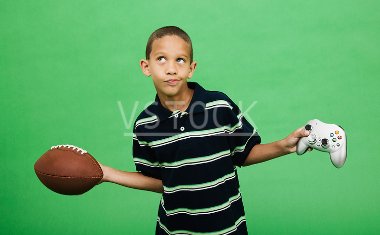 Boy (10-12) holding football and computer joy pad, studio shot