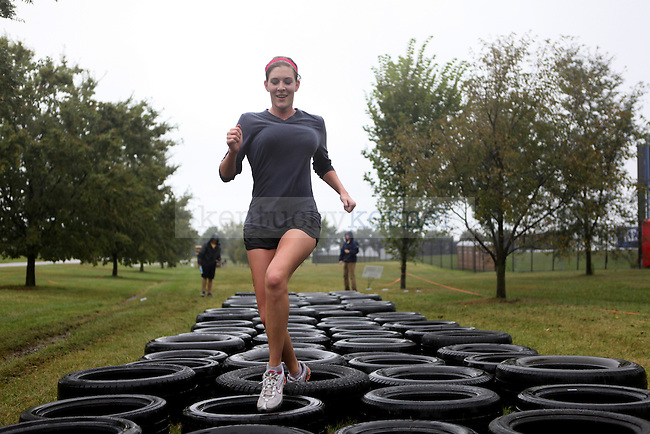 Elementary education senior Bobbie Stewart runs through a tire course during the 2013 Bluegrass Mud Run at Commonwealth Stadium in Lexington, Ky., on Friday, September 20, 2013. Photo by Adam Pennavaria | Staff