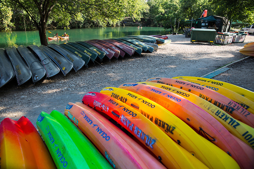 Colorful Kayaks and canoes line the shore at Barton Creek rental as Two Kayakers paddle down the water in Austin, Texas.