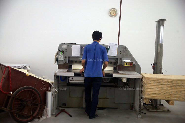 """An Amity Printing Company employee trims reams of Bible pages after printing in the Amity Printing Company's new printing facility in Nanjing, China....On May 18, 2008, the Amity Printing Company in Nanjing, Jiangsu Province, China, inaugurated its new printing facility in southern Nanjing.  The facility doubles the printing capacity of the company, now up to 12 million Bibles produced in a year, making Amity Printing Company the largest producer of Bibles in the world.  The company, in cooperation with the international organization the United Bible Societies, produces Bibles for both domestic Chinese use and international distribution.  The company's Bibles are printed in Chinese and many other languages.  Within China, the Bibles are distributed both to registered and unregistered Christians who worship in illegal """"house churches."""""""