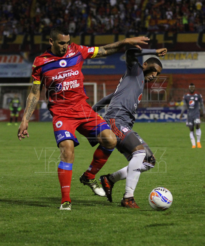 PASTO - COLOMBIA - 24 - 03 - 2018: Gaston Celerino (Izq.) jugador de Deportivo Pasto disputa el balón con Juan Camilo Angulo (Der.) jugador de America de Cali, durante partido Deportivo Pasto y America de Cali, de la fecha 10 por la Liga Aguila I 2018, jugado en el estadio Departamental Libertad de la ciudad de Pasto.  / Gaston Celerino (L) player of Deportivo Pasto fights for the ball with Juan Camilo Angulo (R) player of America de Cali, during a match Deportivo Pasto and America de Cali, of the 10th date for the Liga Aguila I 2018 at the Departamental Libertad stadium in Pasto city. Photo: VizzorImage. / Leonardo Castro / Cont.