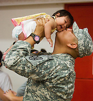 deployment0724 159900-- Specialist Emmanual Bekis kisses his neice Alana Francis, four months, (CQ) before he deployed Thursday with the Phoenix-based 3666th Support Maintenance Company. The Arizona troops will head to Camp Atterbury, Ind., for 30-45 days of training and.then travel to Iraq.  Some of his family came all the way from Red Lake, Arizona, to see him off. (Pat Shannahan/ The Arizona Republic)