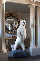 A stuffed polar bear in goggles greets visitors to the columned neo-classical entrance hall to Aynhoe Park