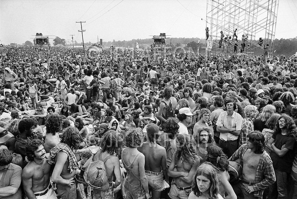 Watkins Glen, NY. July, 1973.<br /> People sitting in the crowd at the Summer Jam at Watkins Glen was a 1973 rock festival which once received the Guinness Book of World Records entry for &quot;Largest audience at a pop festival.&quot; An estimated 600,000 rock fans came to the Watkins Glen Grand Prix Raceway outside of Watkins Glen, New York on July 28, 1973, to see The Allman Brothers Band, Grateful Dead and The Band perform.<br /> Similar to the 1969 Woodstock Festival, an enormous traffic jam created chaos for those who attempted to make it to the concert site. Long and narrow country roads forced fans to abandon their vehicles and walk 5&ndash;8 miles on that hot summer day. 150,000 tickets were sold for $10 each, but for all the other people it was a free concert. The crowd was so huge that a large part of the audience was not able to see the stage; however, twelve huge sound amplifiers, installed courtesy of legendary promoter Bill Graham, allowed the audience to at least hear.