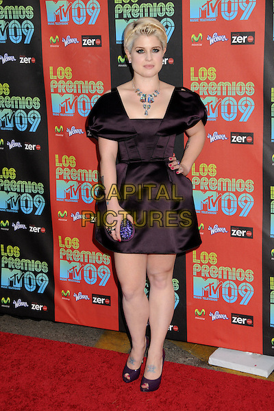 KELLY OSBOURNE.MTV Los Premios Awards 2009 held at the Gibson Amphitheatre, Universal City, California, USA, 15th October 2009..full length black dress peep toe shoes hand on hip tattoos purple pink nails nail varnish polish hand on hip shoulders structured aubergine clutch bag.CAP/ADM/BP.©Byron Purvis/Admedia/Capital Pictures