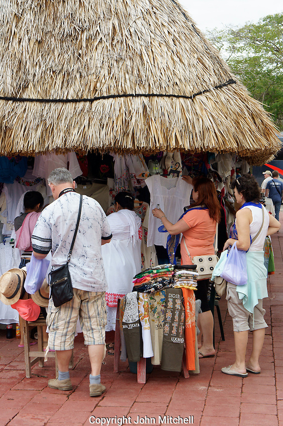 Tourists shopping for clothing and handicrafts outside the Mayan ruins of Uxmal, Yucatan, Mexico..