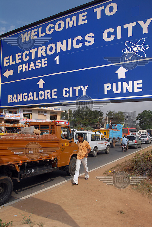 A huge road sign hangs over the entrance to 'Electronics City', an industrial complex dedicated to the IT and electronics industries. The 'Electronics City' complex, located ten miles outside Bangalore, has been hugely successful in attracting foreign investment and it is home to several multinational companies.