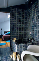 A grey-tiled ensuite bathroom and shower is open to the bedroom