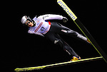 Andreas Kuettel of Switzerland soars through the night sky in the the normal hill individual jump event at the Nordic Skiing World Championships in Sapporo, Japan in March, 2007