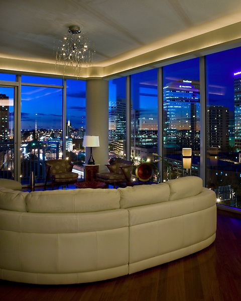 The Scudder condo living room at night with a view of downtown Richmond