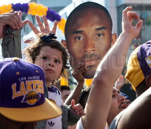 13.04.2016. Los Angeles, California, USA. Maddison Figueroa, 2, is held high by her father Luis, of Montebello, as they join others dance in the streets during Fanfest outside Staples Center on Wednesday in Los Angeles. This was Kobe Bryant's final game.