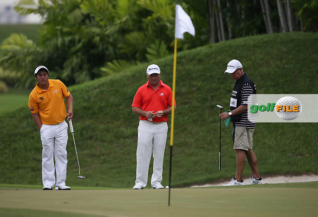 Damien McGrane (IRL) eyes up a birdie putt on the 17th during Round One of the The Championship 2014 from the Laguna National Golf & Country Club, Tampines, Singapore. Picture:  David Lloyd / www.golffile.ie