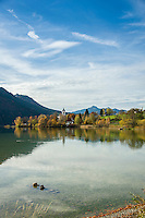 Germany, Bavaria, Swabia, East-Allgaeu, Fuessen: district Weissensee-Oberkirch at Lake Weissensee with parish church St. Walburga - autumn scenery | Deutschland, Bayern, Schwaben, Ost-Allgaeu, Fuessen: Ortsteil Weissensee-Oberkirch am Weissensee mit Pfarrkirche St. Walburga - Herbstlandschaft