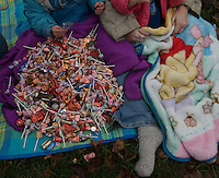 A large bag of candy  sits in the lap of a young girl at the Christmas parade in downtown Westerville, Ohio, on a wet, rainy afternoon. The bag of candy, offered by a grocery store manager, was intended to feed more children but the weather brought a much smaller crowd than expected with the result being more candy for fewer people. Photo Copyright Gary Gardiner. Not for reproduction without written permission.