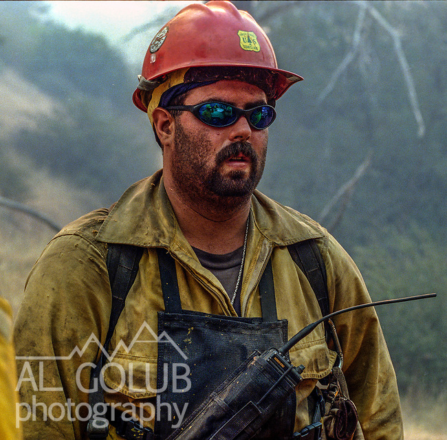 August 16, 1996 Sonora, California  -- Rogge Fire – Stanislaus Hotshot Josh Valentine, covered with dirt from days of firefighting, continues to fight the fire.  The Ackerson and Rogge Fires combined to char 60,000 acres in 1996. The Rogge Fire was centered on the north side of the Tuolumne River, burning over Jawbone Ridge and Cherry Creek areas.