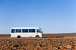 A minibus crosses the lunar like desert landscape of the Moon Plain, near Coober Pedy.  The surreal plain has been the setting for many movies including Mad Max Beyond the Thunderdome, Priscilla Queen of the Desert, and The Red Planet.  Coober Pedy, South Australia, AUSTRALIA.