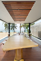 A dining area with plate glass windows opening onto the beach features a spectacular wood table flanked by rows of contemporary stools