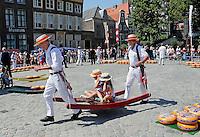 Nederland  Hoorn 2016.  Kaasmarkt in Hoorn.  Kaasdragers dragen jonge toeristen op een berrie. Foto Berlinda van Dam / Hollandse Hoogte