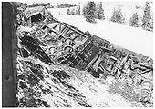 Derailment between Cumbres and Los Pinos at MP 326.  Engines 497 and 498.  View of bottom side of 497.  Another upright engine is seen in distance.  Snow on ground.<br /> D&amp;RGW  between Cumbres &amp; Los Pinos, CO  2/10/1960