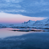 Winter twilight over mountain of Flakstadøy from Fredvang bridges, Lofoten Islands, Norway