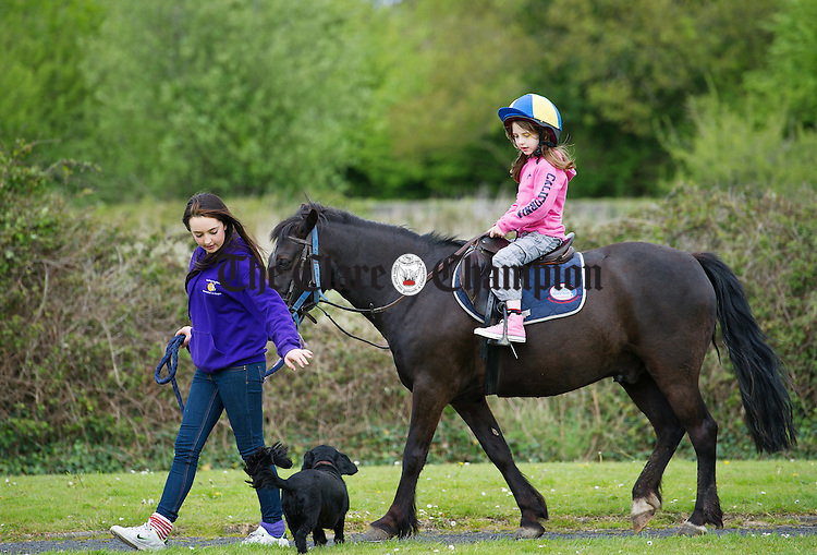 Saoirse Barry leads a young jockey at the Newmarket On Fergus Family Fun Day in O Regan Park. Photograph by John Kelly.