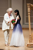 USA International Harp Competition Vice President Linda Wood Rollo gives flowers to performer Yuet Kan during the Stars of Tomorrow Concert at the 11th USA International Harp Competition at Indiana University in Bloomington, Indiana on Thursday, July 11, 2019. (Photo by James Brosher)